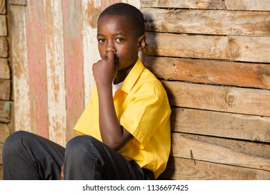 Close up of a black boy looking straight into the camera while he is sitting in his school clothes