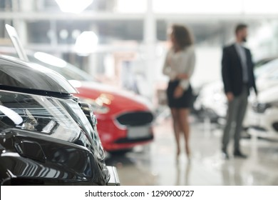 Close up of black car headlight. Modern showroom with expensive automobiles. People standing in car center, looking for and choosing vehicles. Woman and man observing auto for purchase.
