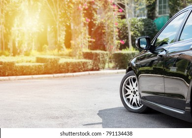 Close up of black car parked on the asphalt road and front view garden with sunlight.