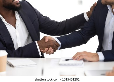 Close up black and caucasian business partners shake hands at group meeting. Handshake symbol of respect and trust. Teamwork introduction, partnership, effective negotiations, first impression concept