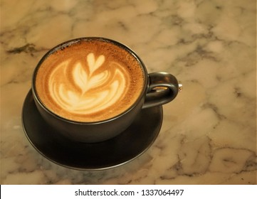 Close up black coffee cup with latte art foam on marble table, Hua Hin Thailand.