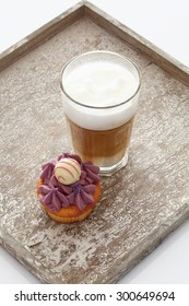 Close up of black currant buttercream cupcake with glass of latte macchiato on tray