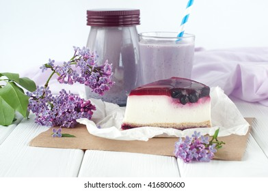 Close up of black current cheesecake slice near bilberry milkshake and lilac flowers on the white wooden background. Selective focus and small depth of field.