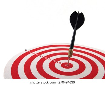 close up black dart arrow hitting on target center on bullseye in dartboard on white background, perfection goal success, symbol of aim and achievement