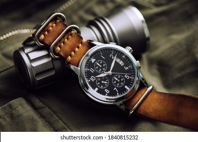 Close up black dial military style wristwatch with black leather watch band. Wristwatch for men with military objects in the background.