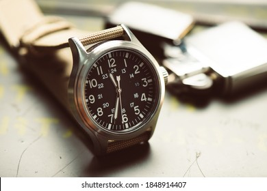 Close up black dial military style wristwatch with biege nylon watch band. Wristwatch for men with military objects in the background.