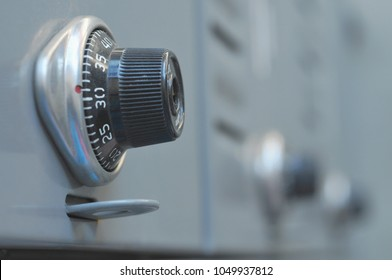 Close up black dial twisting combination lock with silver bezel on gray locker showing blurred line of lockers in background. Good for school, gym, airport or workplace belongings concept