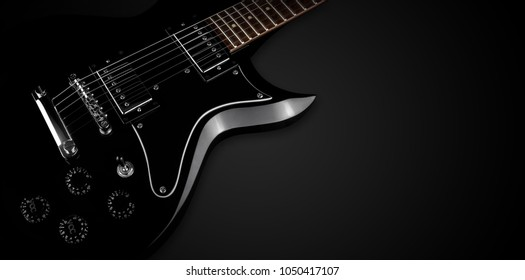 close up black electric guitar on black background concept