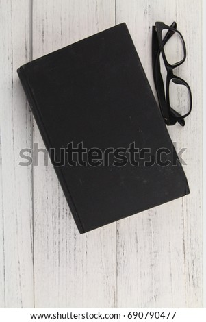 93b15081983c Close up Black Eye Glasses with a thick black book over wooden texture  background. Copy