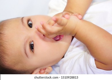 Close up black eyes of little cute Asian baby (about 4-6 months) lying on a blue bed sheet and keeps fingers in his mouth. Happy childhood, cherished and love concept.