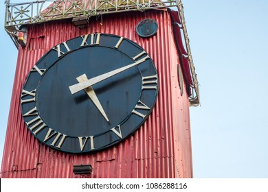 A close up of the black face of Ali Amjad's Clock the British Empire era red tin clock tower, a popular tourist attraction in downtown Sylhet.