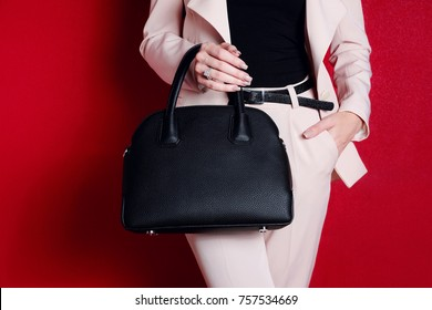 Close up of black fashion bag in hand of trendy woman. Female accessories.