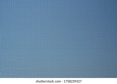 Close up of black fly screen with blue cloudless sky in background. Mosquito net fixed on a window. Insect screen. Contre-jour shot.