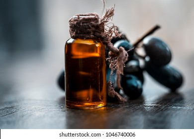 Close up of Black grapes oil on a wooden surface in dark  Gothic colors  to improve overall hair growth.It is rich in source of vitamin A,K and C along with flavonoids and minerals.
