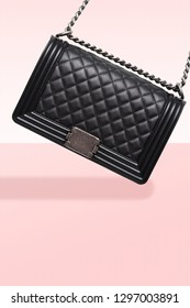 Close - up of black handbag on pink background. Steel chain and leather with diamonds. Luxurious accessory