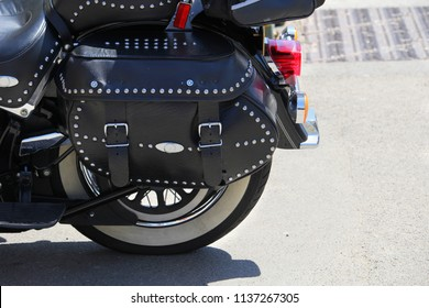 Close up of a black leather strapped and studded motorcycle pannier or bag, on a sunny day