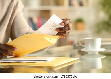 Close up of a black man hands opens a yellow padded envelope with letter sitting ona desk at home