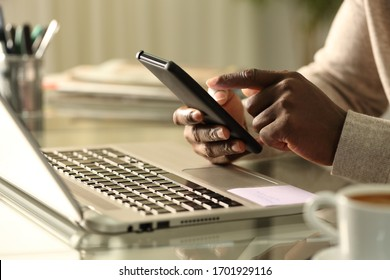 Close up of black man hands using smart phone with laptop at home