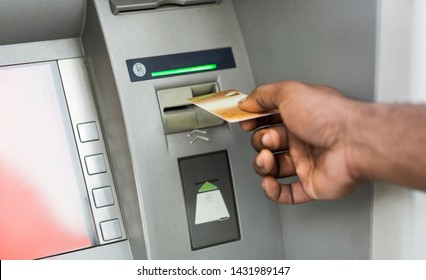 Close up of black man using ATM with gold credit card, panorama, copy space
