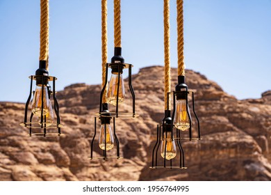 """Close up black metal bulbs hunging on ropes in the middle of the mountains in """"Al Ola"""" Al Ula, Saudi Arabia. Al Ola is Part of Madinah Province in Western Saudi Arabia"""