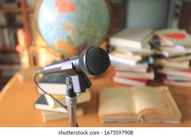 A close up of a black microphone in the classroom A pile of books in the background selective focus and shallow depth of field