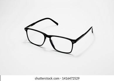 Close up black modern style eyeglasses with transparent lenses for businessman isolated on white background with shadow.