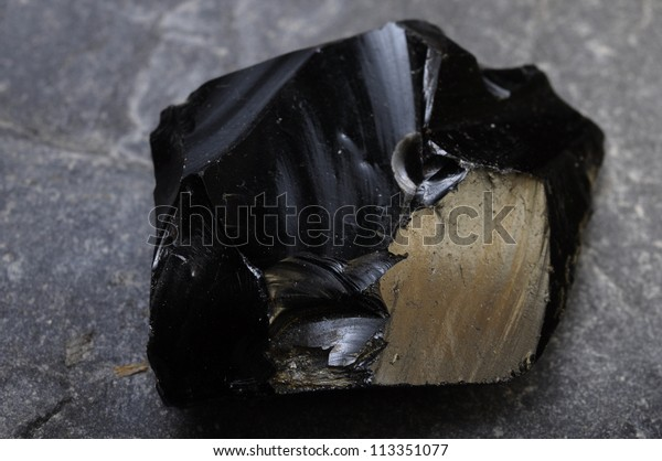 Close up of a black obsidian stone on mineral background