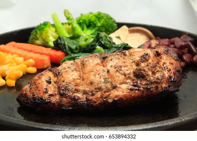 Close up of black pepper chicken steak and vegetables