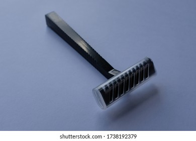 Close Up of Black Plastic Disposable Shaving Razor, Cheap Tool, Isolated on Plain White Background, With Clear Plastic Cover