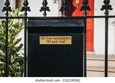 """Close up of a black post box with """"no free newspapers or junk mail"""" sign outside a house on a fence on a sunny day."""