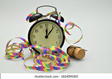 close up of  a black retro twin bell alarm clock, around midnight, with paper streamers and cork from a bottle of sparkling wine