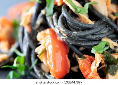 Close up of black spaghetti with cherry tomatoes, tuna and parsley.