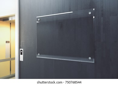 Close up of black tile wall with empty glass billboard in interior with elevator. Success, startup, advertising concept. Mock up, 3D Rendering