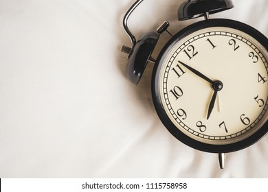 Close up black vintage alarm clock on white fabric show before eight o'clock, clock in the morning with copy space