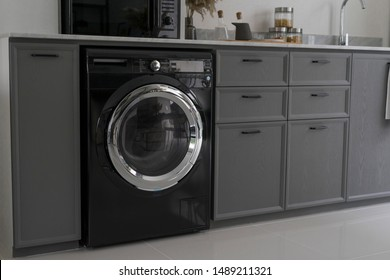 Close up of black washing machine installed in home kitchen counter