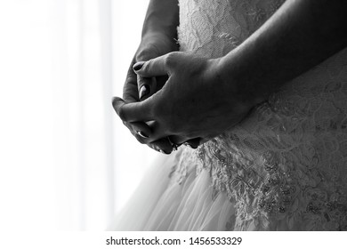 Close up black and white of Bride in white lace gown standing in front of window with hands clasped together showing only her midsection and displaying engament ring before the wedding ceremony