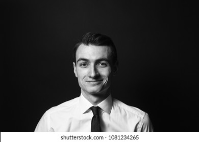 Close up black and white portrait of a young man in a white shirt and black tie, smiling while looking at the camera, against plain studio background