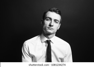 Close up black and white portrait of a young man in a white shirt and black tie, seriously looking at the camera, against plain studio background