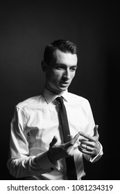 Close up black and white portrait of a young man in a white shirt and black tie, talking and looking to the side, against a plain studio background