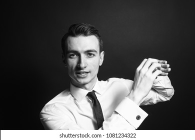 Close up black and white portrait of a young man in a white shirt and black tie, talking and explaining with his hands, against a plain studio background