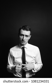Close up black and white portrait of a young man in a white shirt and black tie, talking and looking at the camera, against a plain studio background