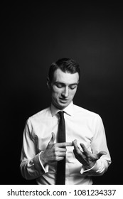 Close up black and white portrait of a young man in a white shirt and black tie, counting with his fingers and talking, against a plain studio background
