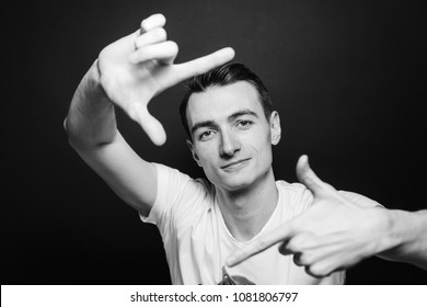 Close up black and white portrait of a young man in white shirt, looking at the camera through his hands, against plain studio background