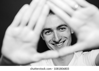Close up black and white portrait of a young man in white shirt, laughing, looking at the camera through his hands, against plain studio background