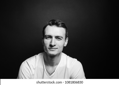 Close up black and white portrait of a young man in white shirt, looking at the camera, against plain studio background