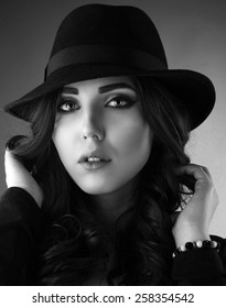 Close up black and white portrait of a young woman wearing a hat