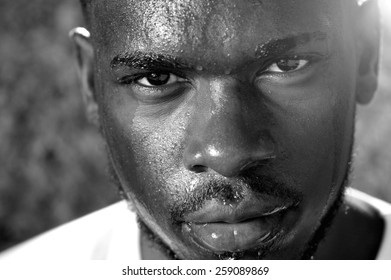 Close up black and white portrait of a young man sweating with intense look of face