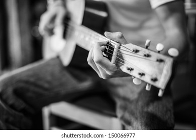 Close up black and white shot of a persons hand playing and old acoustic guitar