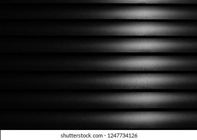 Close up Black window blinds with light, Dark background