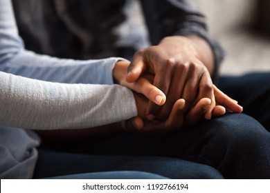 Close up black woman and man in love sitting on couch two people holding hands. Symbol sign sincere feelings, compassion, loved one, say sorry. Reliable person, trusted friend, true friendship concept
